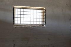 Alte weiße Wand mit dem Fenster bedeckt durch Eisengitter Sun, der durch Grill scheint Gefängnisrauminnenraum Enlightment-Konzept Stockfotografie