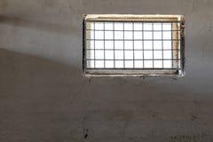 Alte weiße Wand mit dem Fenster bedeckt durch Eisengitter Sun, der durch Grill scheint Gefängnisrauminnenraum Enlightment-Konzept Lizenzfreie Stockfotografie
