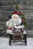 Alte Weihnachtsdekoration: Weihnachtsmann und ein altes Zinn spielt Autoesprit Lizenzfreies Stockbild
