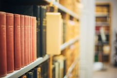 Alte Weinlese-Bücher auf hölzernem Shelfs in der Bibliothek Lizenzfreie Stockfotos