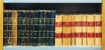 Alte Weinlese-Bücher auf hölzernem Shelfs in der Bibliothek Stockfotografie