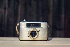 Alte Weinlese goldene Kamera Penti I auf hölzernem Hintergrund Stockbilder