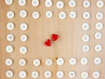 Alte Weinlese knöpft Rahmengrenze mit zwei roten hölzernen Herzen in der Mitte Nähen, Hobby, Lebensstilkonzept Lizenzfreies Stockfoto