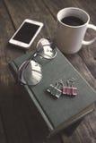 Alte Weinlesebücher, -Smartphone und -gläser auf einem Holztisch Lizenzfreie Stockfotos