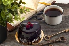 Alte Weinlesebücher, Tasse Tee, Kuchen und Schlüssel auf rustikalem Holztisch Stockfotos