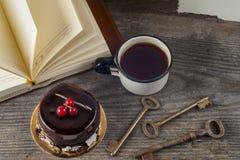 Alte Weinlesebücher, Tasse Tee, Kuchen und Schlüssel auf rustikalem Holztisch Stockbilder