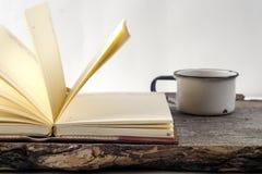 Alte Weinlesebücher, Tasse Tee, Kuchen und Schlüssel auf rustikalem Holztisch Lizenzfreie Stockbilder