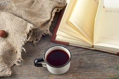 Alte Weinlesebücher, Tasse Tee, Kuchen und Schlüssel auf rustikalem Holztisch Lizenzfreie Stockfotos