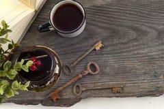 Alte Weinlesebücher, Tasse Tee, Kuchen und Schlüssel auf rustikalem Holztisch Lizenzfreies Stockfoto