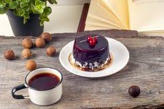 Alte Weinlesebücher, Tasse Tee, Kuchen und Schlüssel auf rustikalem Holztisch Stockbild