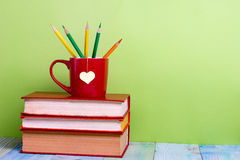Alte Weinlesebücher und -schale mit Herzen formen auf Holztisch Zurück zu Schule Stockfotos