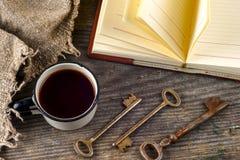 Alte Weinlesebücher und -schale mit Tee und -schlüssel auf Tabelle auf rustikalem hölzernem Hintergrund Lizenzfreie Stockfotos