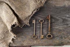 Alte Weinlesebücher und -schlüssel auf Tabelle auf rustikalem hölzernem Hintergrund Lizenzfreie Stockbilder