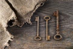 Alte Weinlesebücher und -schlüssel auf Tabelle auf rustikalem hölzernem Hintergrund Stockfotos