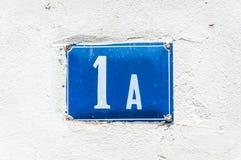 Alte Weinlesehaus-Adreßmetallplattenzahl 1 A auf der Gipsfassade der verlassenen Ausgangsaußenwand auf der Straßenseite Stockfoto