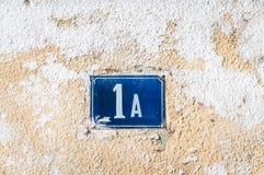 Alte Weinlesehausadreßblaue Metallzahl 1 A eins auf der Gipsfassade der verlassenen Hauptaußenwand auf der Straßenseite stockbild