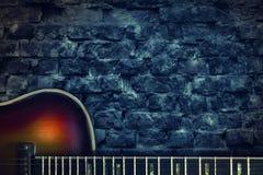 Alte Weinlesejazzgitarre auf einem Backsteinmauerhintergrund Kopieren Sie Platz Hintergrund für Konzerte, Festivals, Musikschulen stockbild