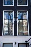 Alte Weinleselaterne zwischen zwei Fenstern im traditionellen niederländischen Arthaus stockfoto