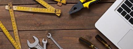 Alte Werkzeuge und Computer auf Holztisch Lizenzfreies Stockbild