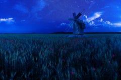Alte Windmühle auf Nachtweizen-Feld Stockfotografie