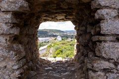Alte Windmühle durch kleines Fenster in der Festungswand, Obidos Lizenzfreie Stockbilder