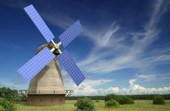 Alte Windmühle mit Sonnenkollektoren auf seinen Flügeln Stockbilder