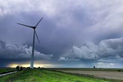 Alte Windmühle und moderne Turbinen am Sturm lizenzfreies stockfoto