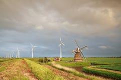 Alte Windmühle und Turbinen bei regnerischem Sonnenuntergang lizenzfreie stockfotos