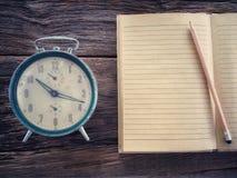 Alte Winduhr mit Notizbuch und Bleistift auf hölzerner Tabelle im Weinlesefarbschema Lizenzfreie Stockfotos