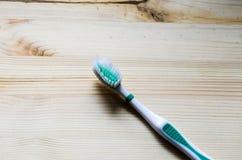 Alte Zahnbürste auf hölzernem Hintergrund Film- Ton Stockbild