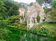 Alte zerbröckelnde Gebäude des Steins auf einem kleinen Fluss der Nymphe im Garten der Nymphe in Italien Lizenzfreies Stockbild