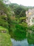 Alte zerbröckelnde Gebäude des Steins auf einem kleinen Fluss im Garten der Nymphe in Italien Lizenzfreies Stockbild