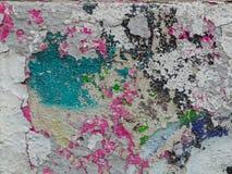 Alte, zerbröckelnde Wand mit mehrfarbiger Farbe spritzt lizenzfreie stockbilder