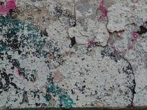 Alte, zerbröckelnde Wand mit mehrfarbiger Farbe spritzt stockbilder
