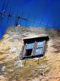 Alte zerbrochene Fensterscheibe mit Antenne und blauem Himmel ein verlassenes Haus in Bakar, Kroatien Stockfotos