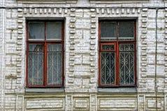 Alte zerbrochene Fensterscheiben mit einem Gitter auf der Backsteinmauer des Gebäudes Stockfoto