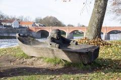 Alte Ziegelsteinbrücke über dem Fluss Venta in der Stadt von Kuldiga Lettland und hölzerner Fischer im Boot stellen auf Front dar lizenzfreies stockbild