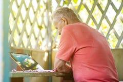 Alter älterer Mann im Ruhestand, der an einer Laptop-Computer in der Sommernische arbeitet lizenzfreie stockbilder