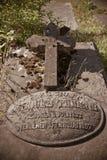 Alter überwucherter Grundstein auf einem Grab Stockbild