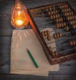 Alter Abakus, das Papier mit einem Bleistift nahe bei Lampe Stockfotos
