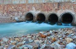 alter Abfluss in der Dämmerungszeit und im flüssigen Wasser Stockfotografie