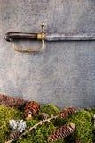 Alter antiker Säbel mit Waldstillleben auf grauem Hintergrund, historische Waffen Stockfotografie