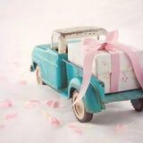 Alter antiker Spielzeuglastwagen, der eine Geschenkbox mit rosa Band transportiert Stockbilder