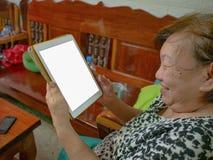 Alter asiatischer Frauen sehr glücklicher Blick auf die Tablette stockfotos