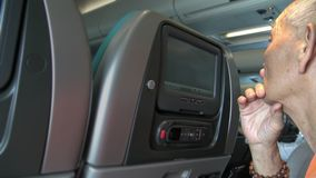 alter asiatischer Passagier des Mannes 4k auf einem Flugzeug unter Verwendung des Schirmmonitors für Uhr ein Film stock footage