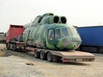 Alter auseinandergebauter Militärhubschrauber auf dem LKW-Anhänger stockbild