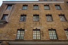 Alter Backsteinbau mit vielen Fenstern Stockbilder