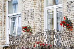Alter Balkon des Backsteinhauses mit Blumen Stockbilder