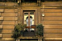 Alter Balkon wird mit Zierpflanzen verziert In den Fenstern von Türen eines Balkonfensters gegenüber von wird reflektiert Lizenzfreie Stockfotografie