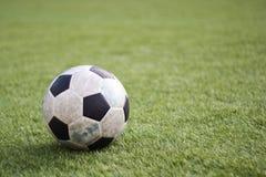 Alter Ball auf neuem Rasen Stockbilder